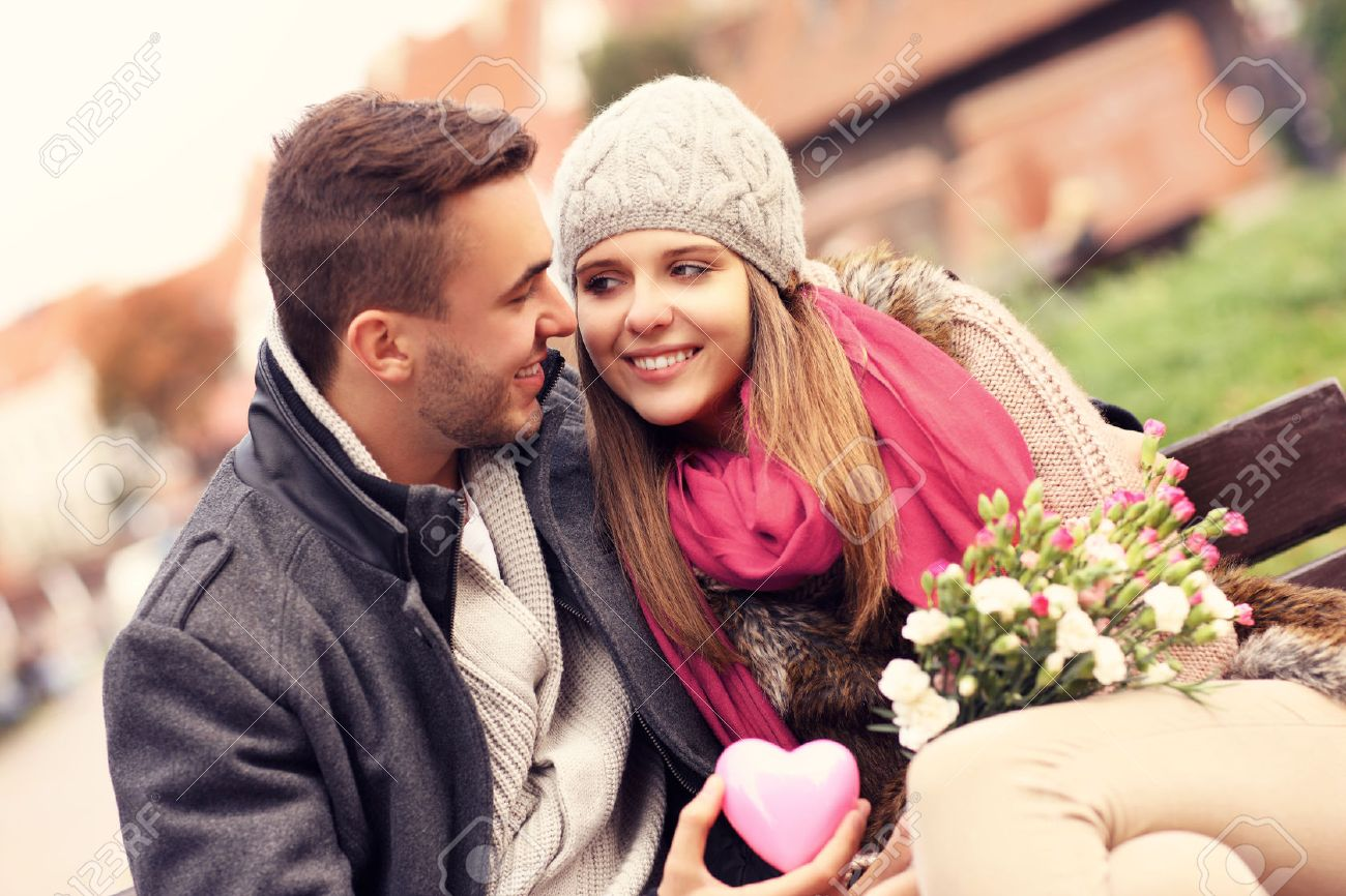 a picture of a couple on valentine s day in the park with flowers
