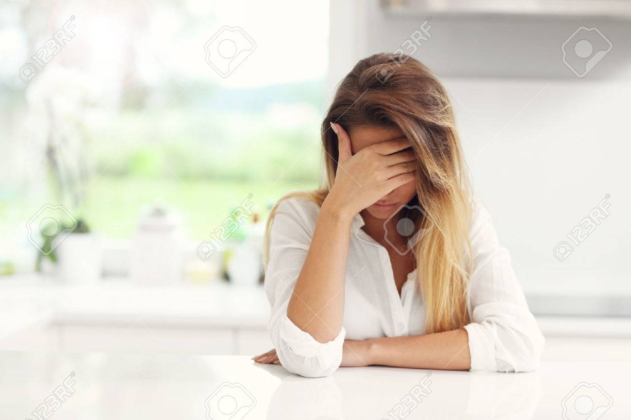 Picture of young sad woman in the kitchen - 61300034