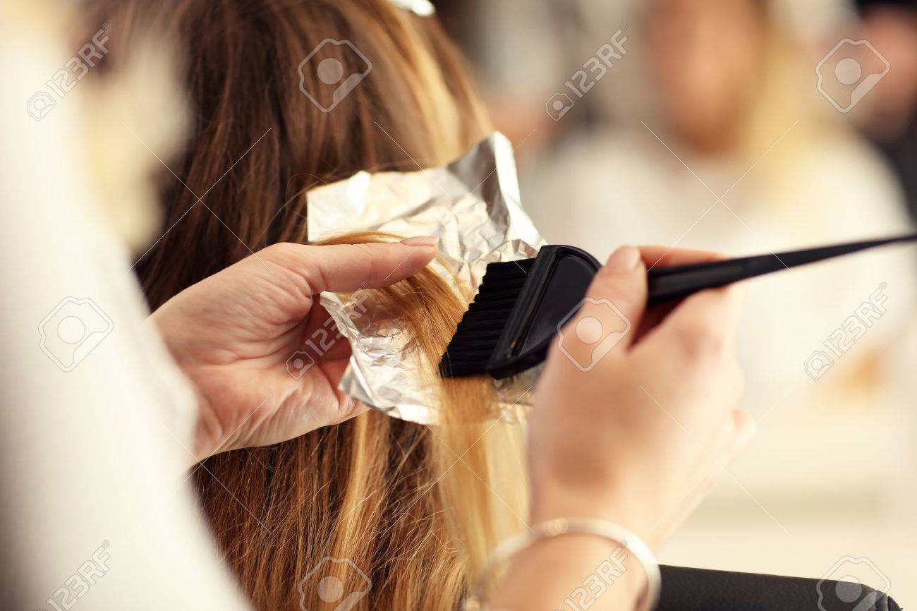 Picture showing hairdresser coloring hair in studio - 67403769