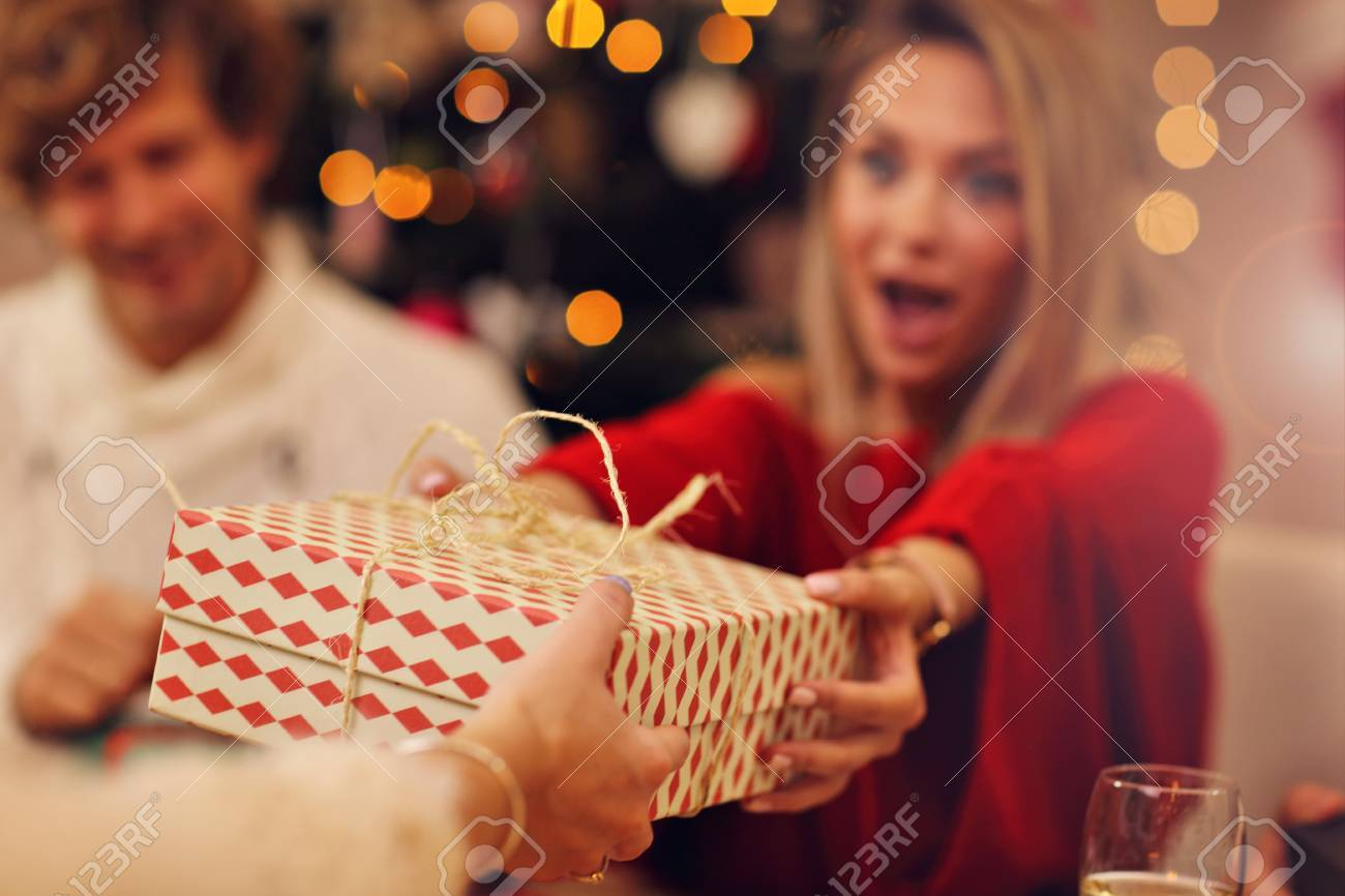 Group of friends giving Christmas presents at home - 88070673