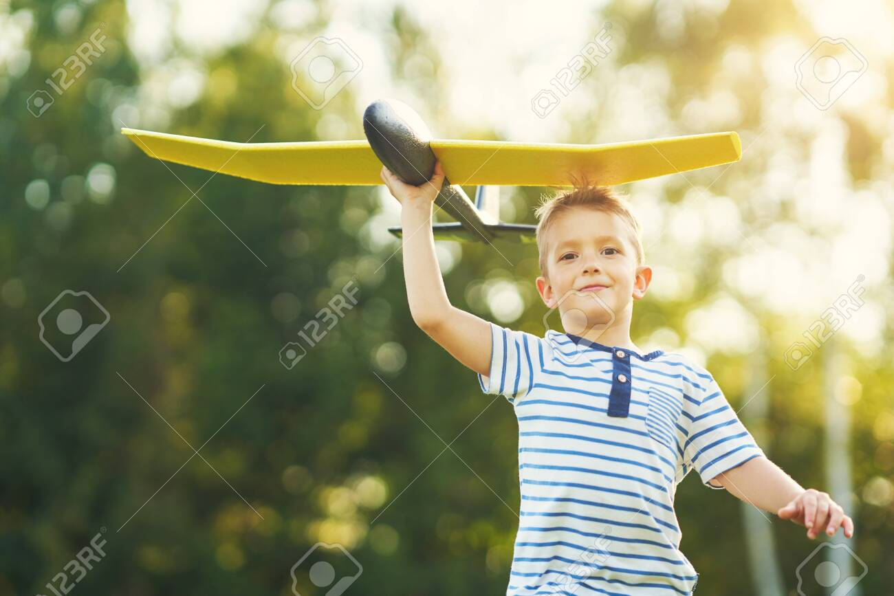 Happy 3 year old boy having fun playing with big plane outdoors - 128517556