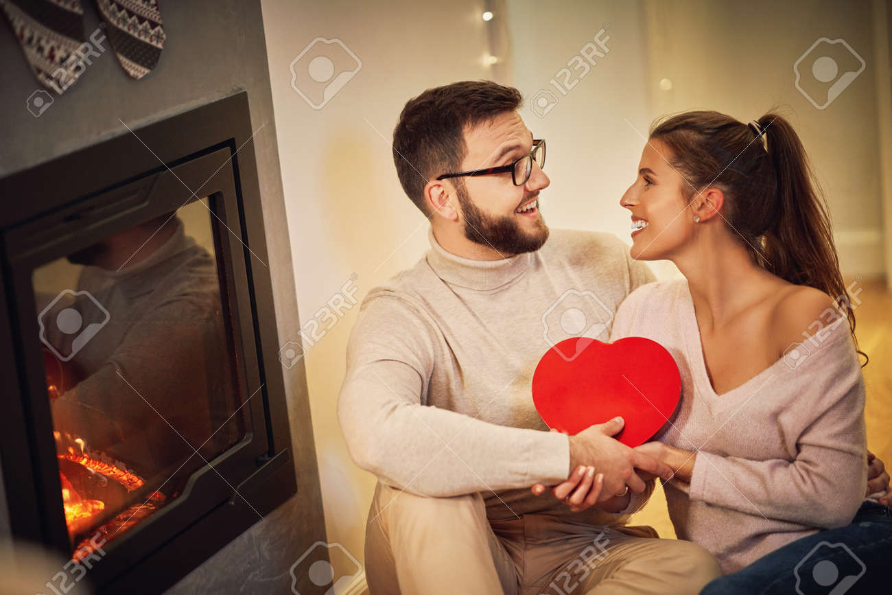 Adult couple with present over fireplace - 157754064