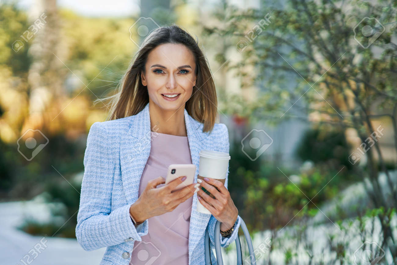 Adult attractive Business woman with smartphone and coffee walking in the city - 169882315