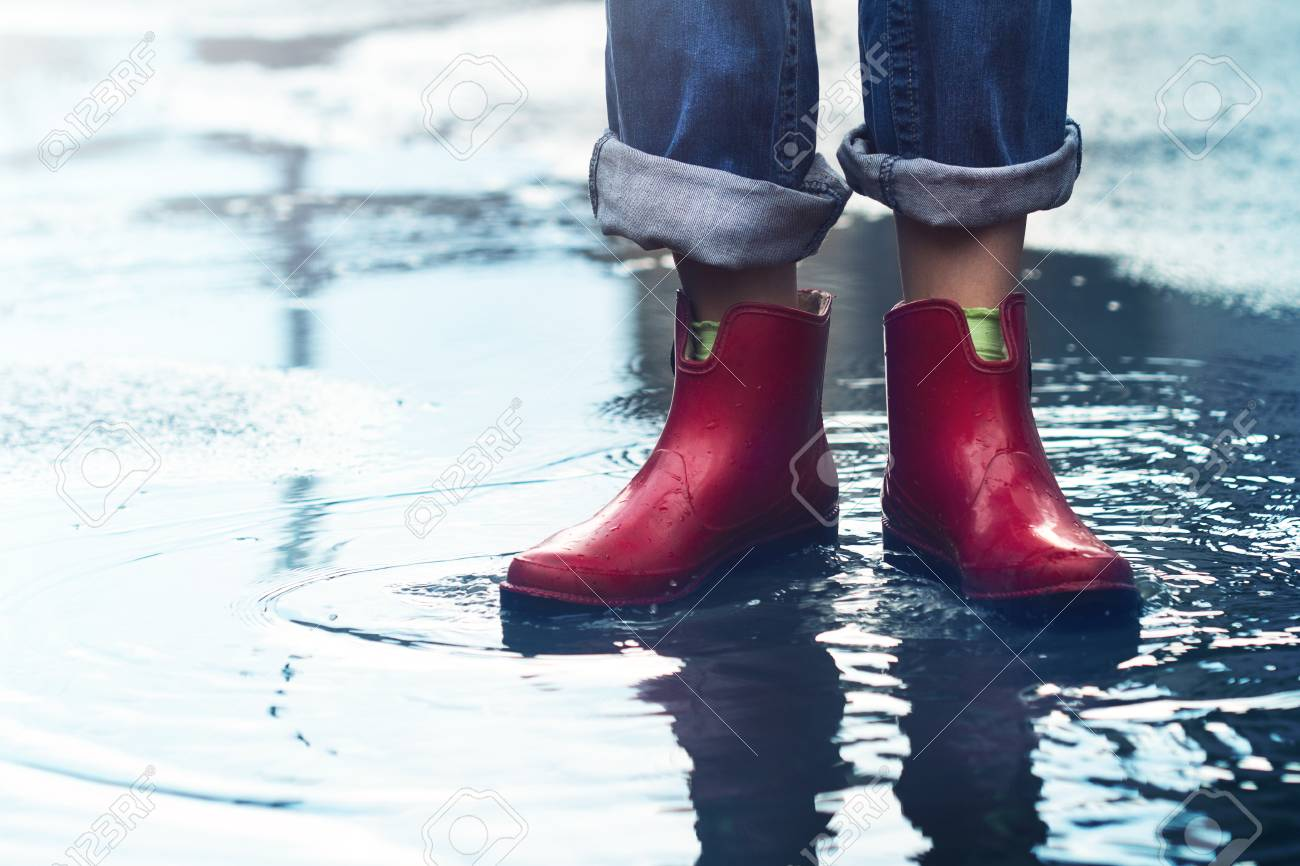 e268d27aca14 front view closeup of young Caucasian woman feet with red short rubber boots  and blue jeans