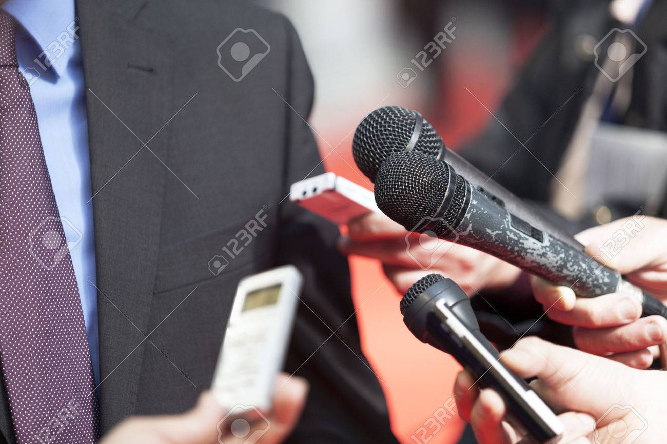 A journalist is making a interview with a microphone - 26822703
