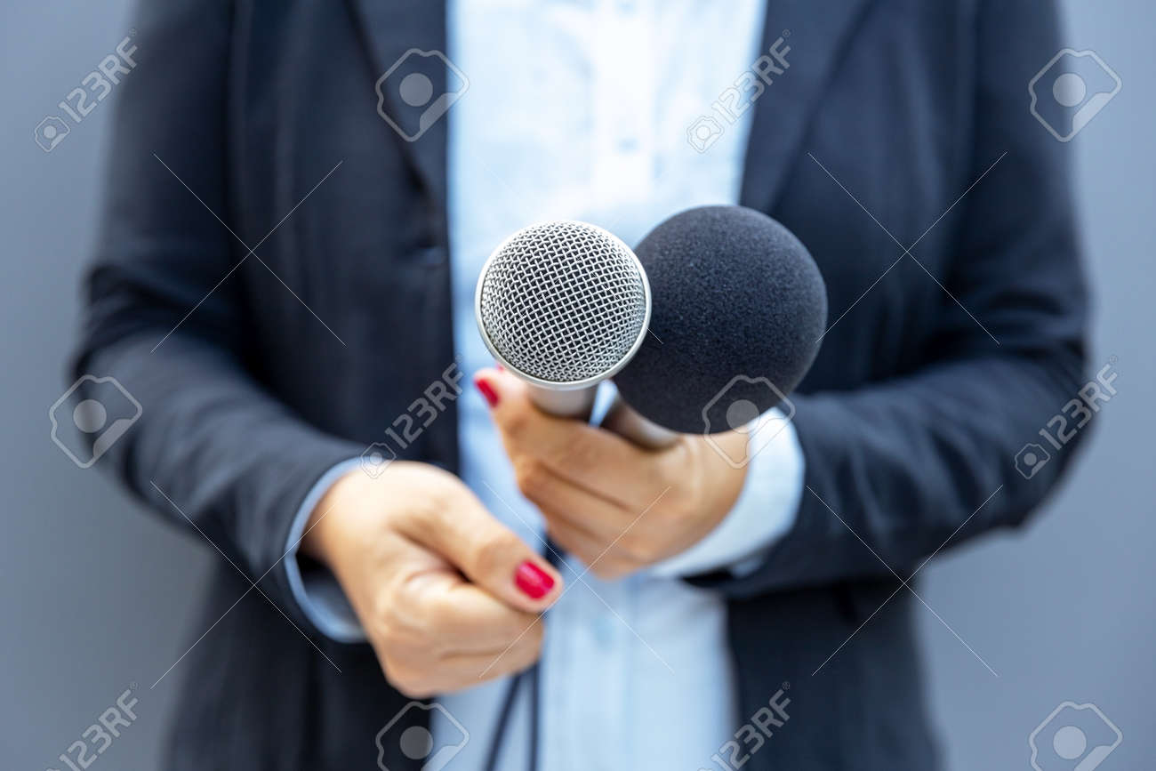 Television reporter holding microphone during press interview. Journalism concept. - 157063267
