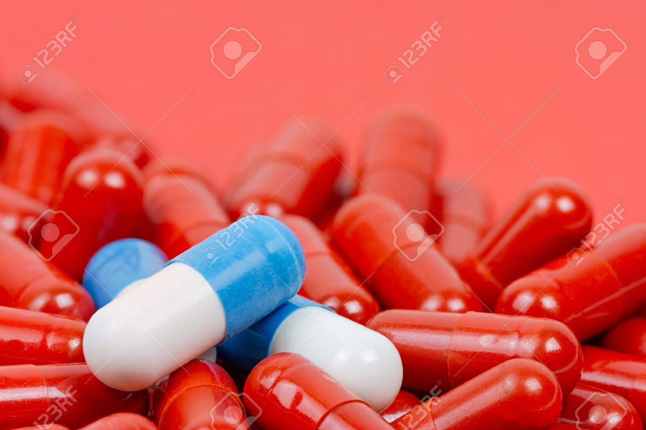 Blue and white pills on background of red pills - 20556353