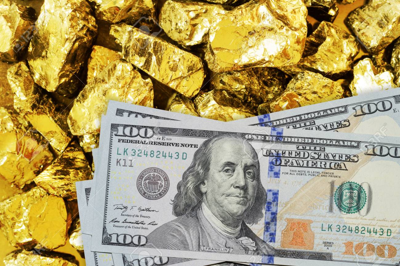 One hundred dollar banknotes on gold mine close up. Mining industry concept with dollars and gold - 110302794