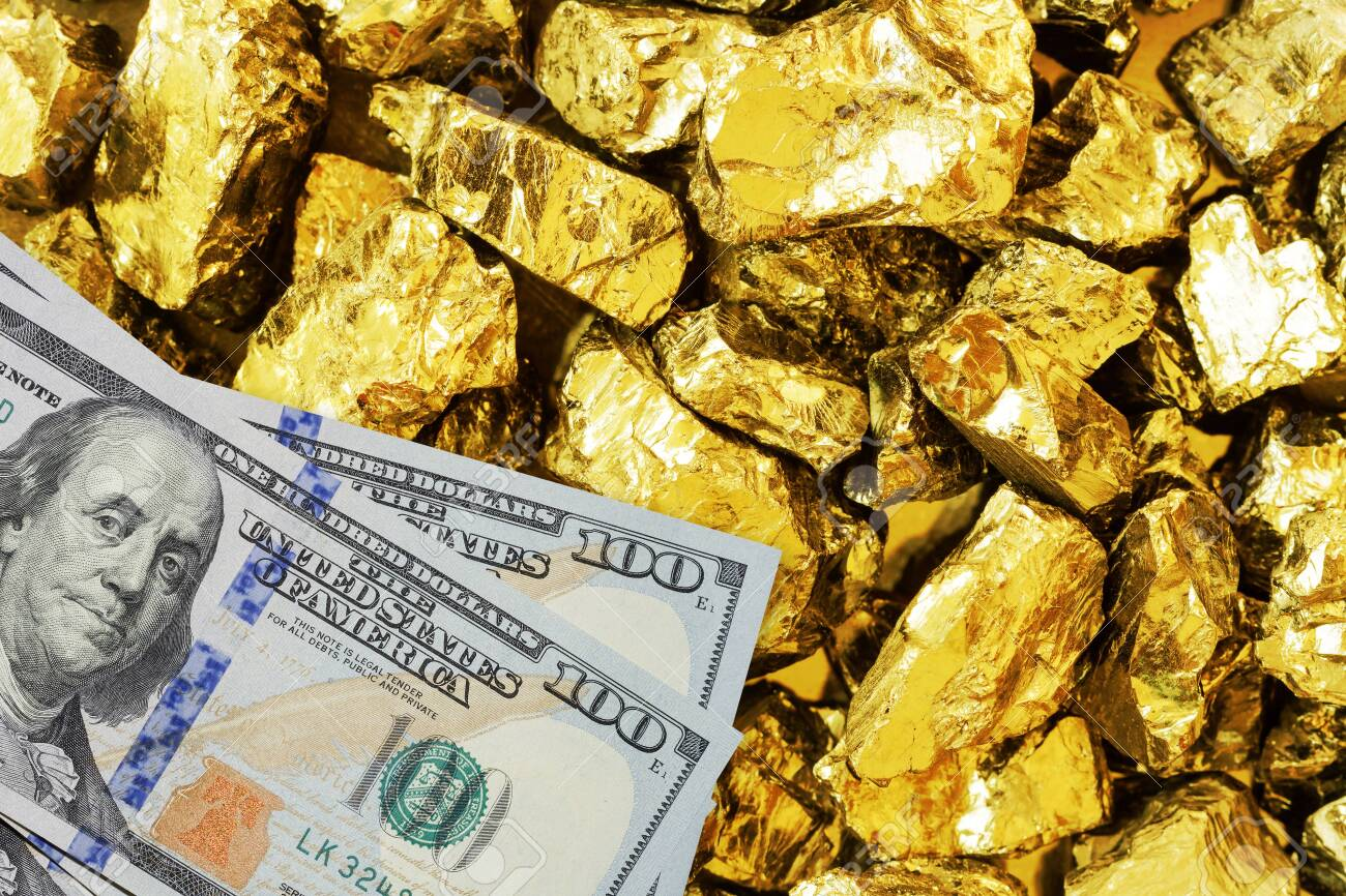 One hundred dollar banknotes on gold mine close up. Mining industry concept with dollars and gold - 110303607