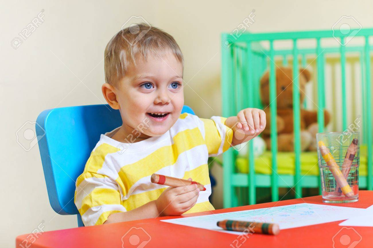 Little cute boy draws with crayons in the nursery Stock Photo - 9213692