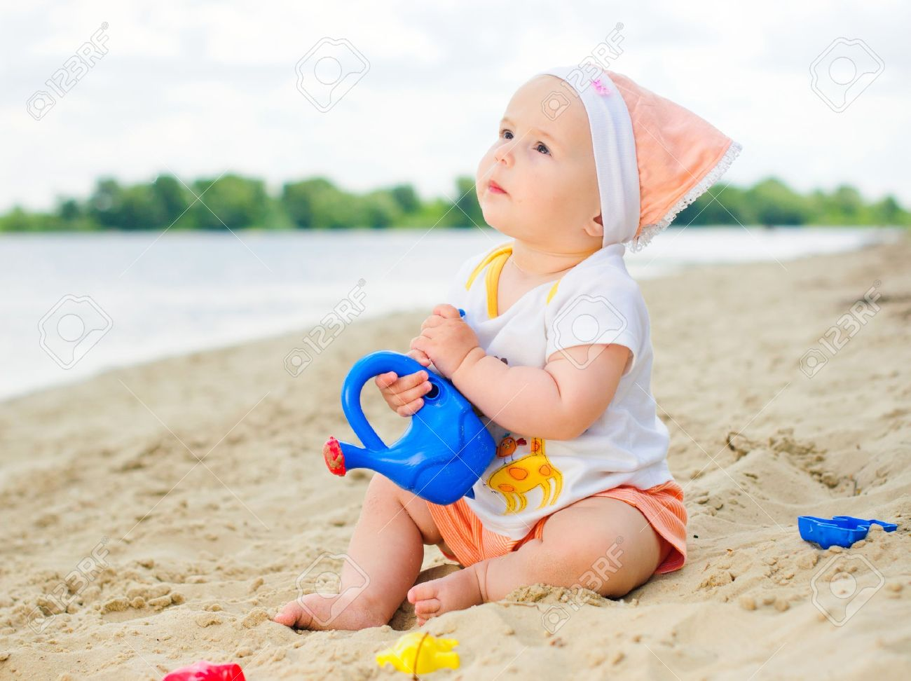 baby girl playing on the beach with sand. Stock Photo - 12370134