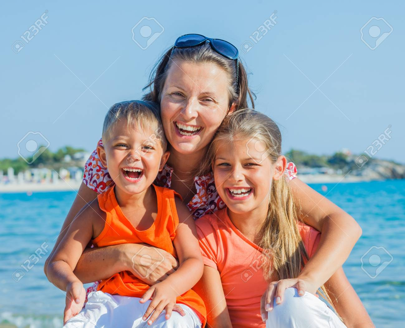 Portrait of happy family laughing and looking at camera on the beach Stock Photo - 17497750