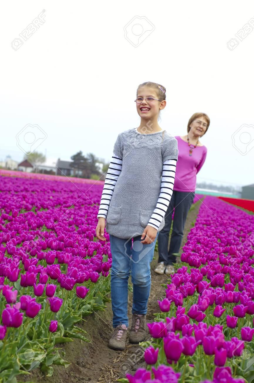Girl with her grandmother walks between of the purple tulips field Stock Photo - 17858724