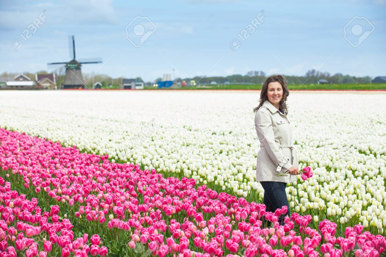 Young woman with bouquet between of the white-purple tulips field Stock Photo - 18238989
