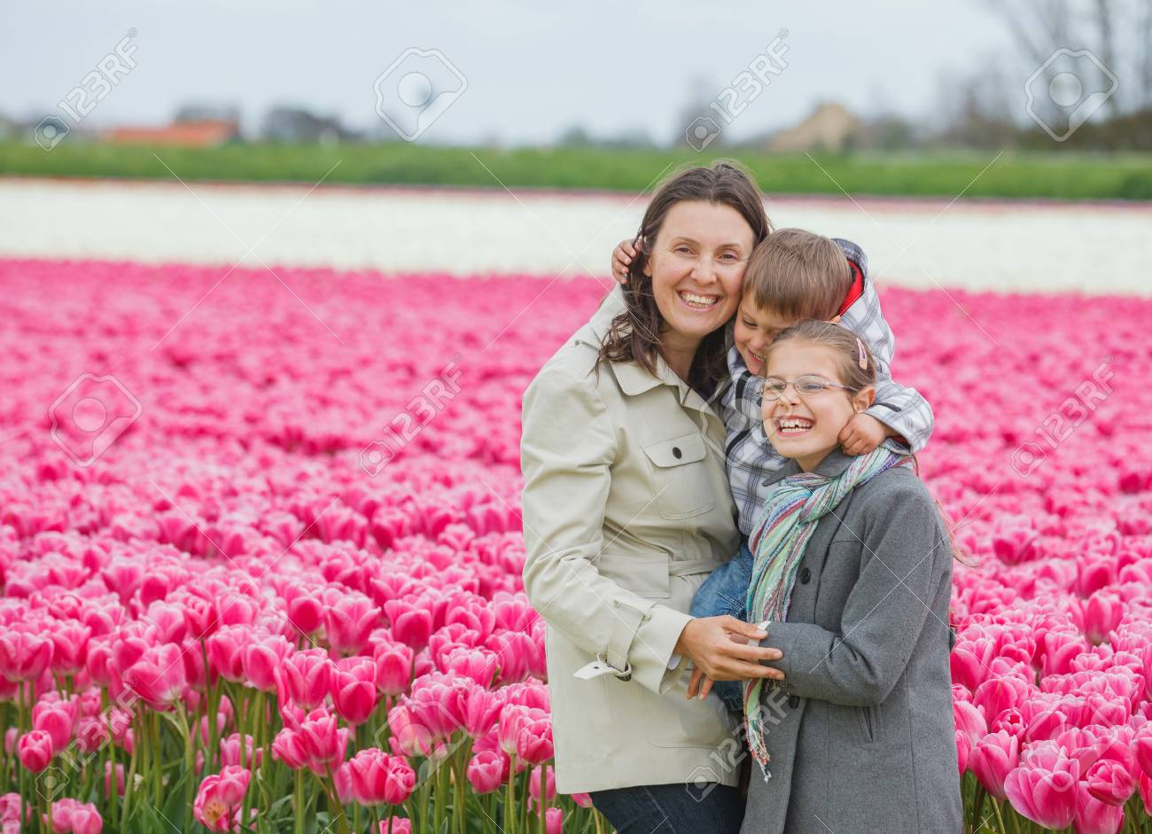 Mother with her child walks between of the purple tulips field Stock Photo - 18241242