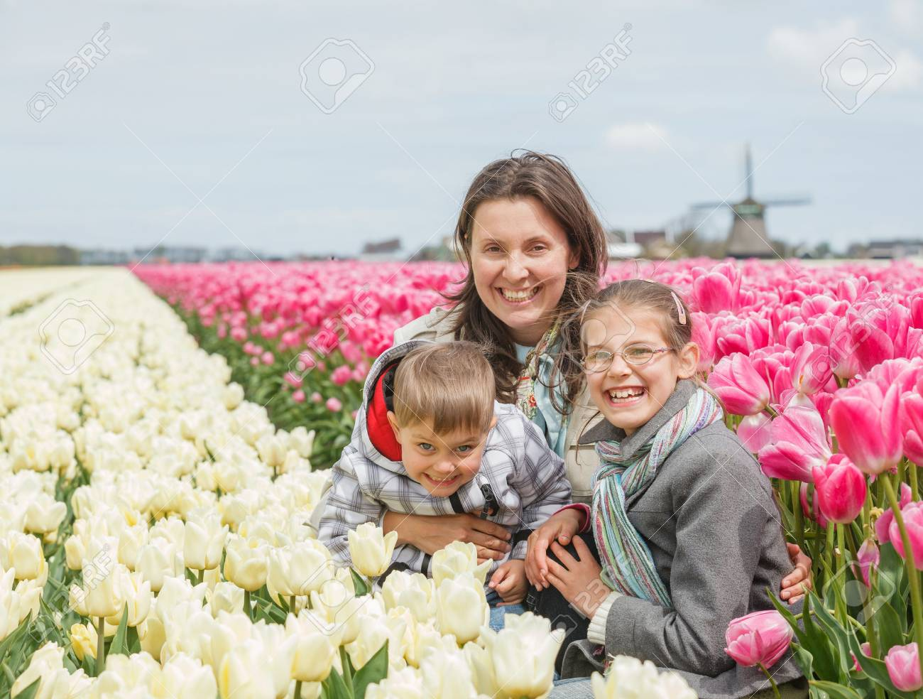Mother with her child sits between of the white and purple tulips field Stock Photo - 18241250