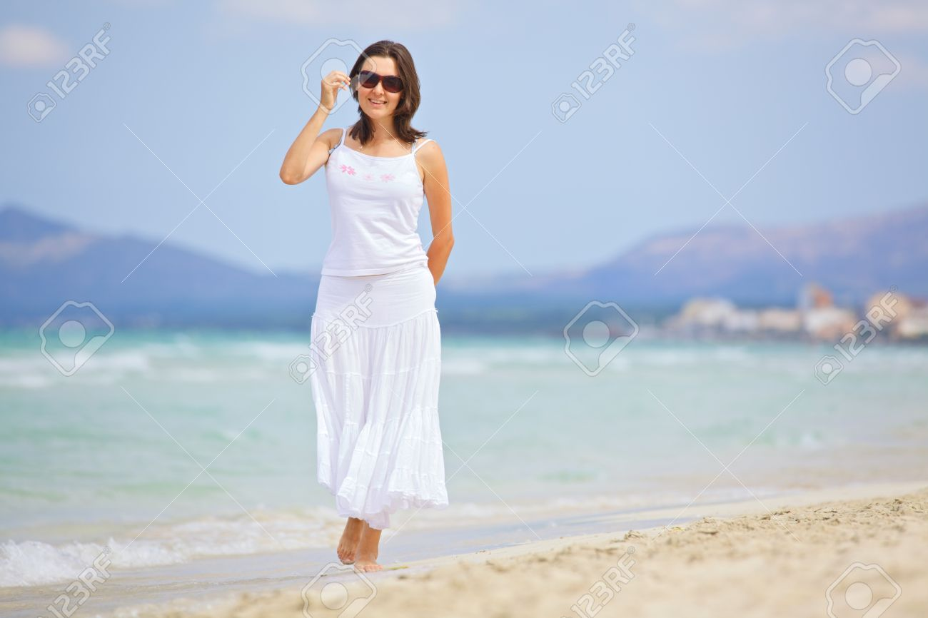 Woman walking on a beach royalty - Beautiful Young Woman Walking On The Beach Enjoying The Sun Stock Photo 18847975