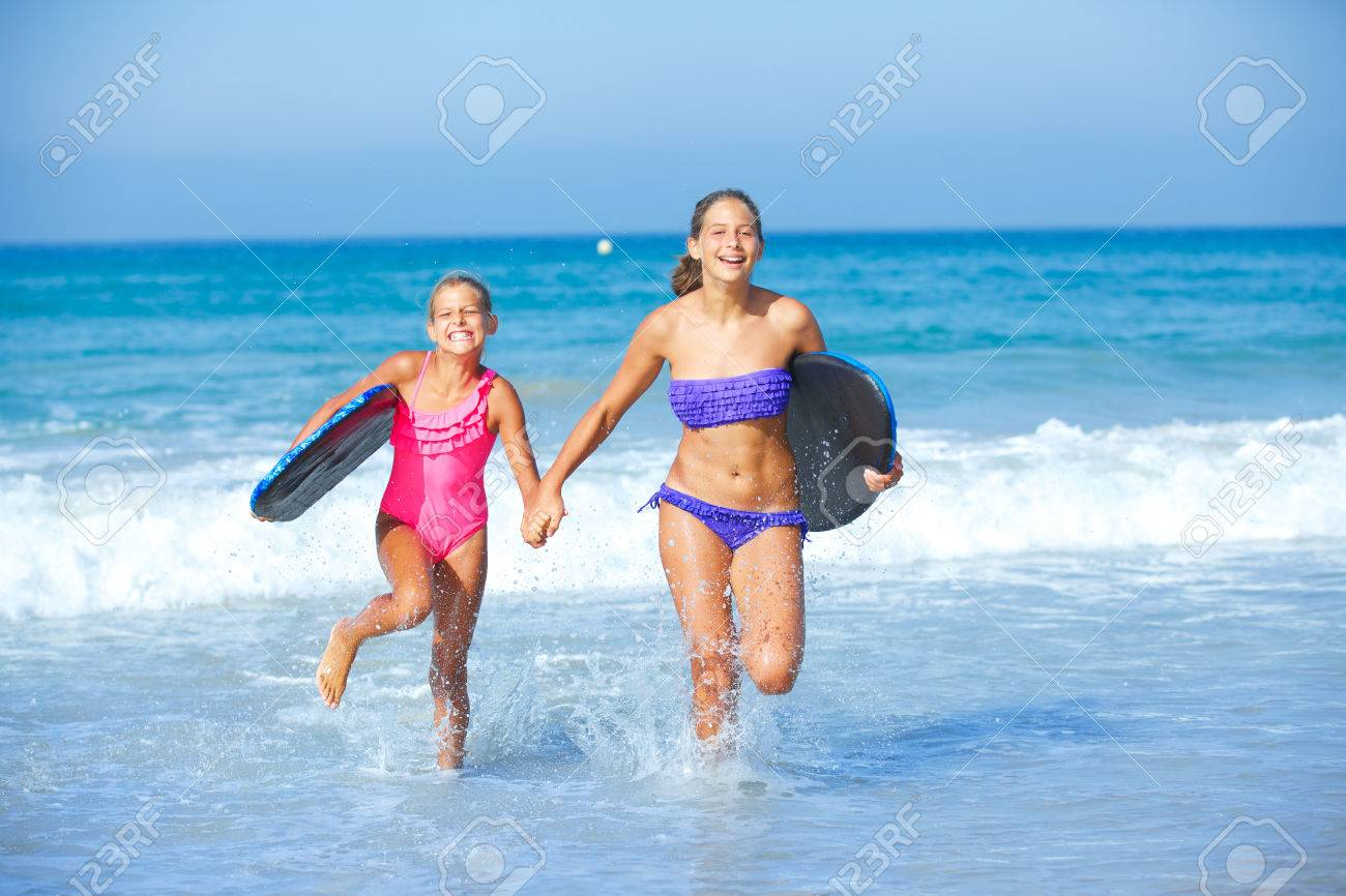 94d6d80532bf3 Summer vacation - Two cute girls in bikini with surfboard running from the  ocean Stock Photo