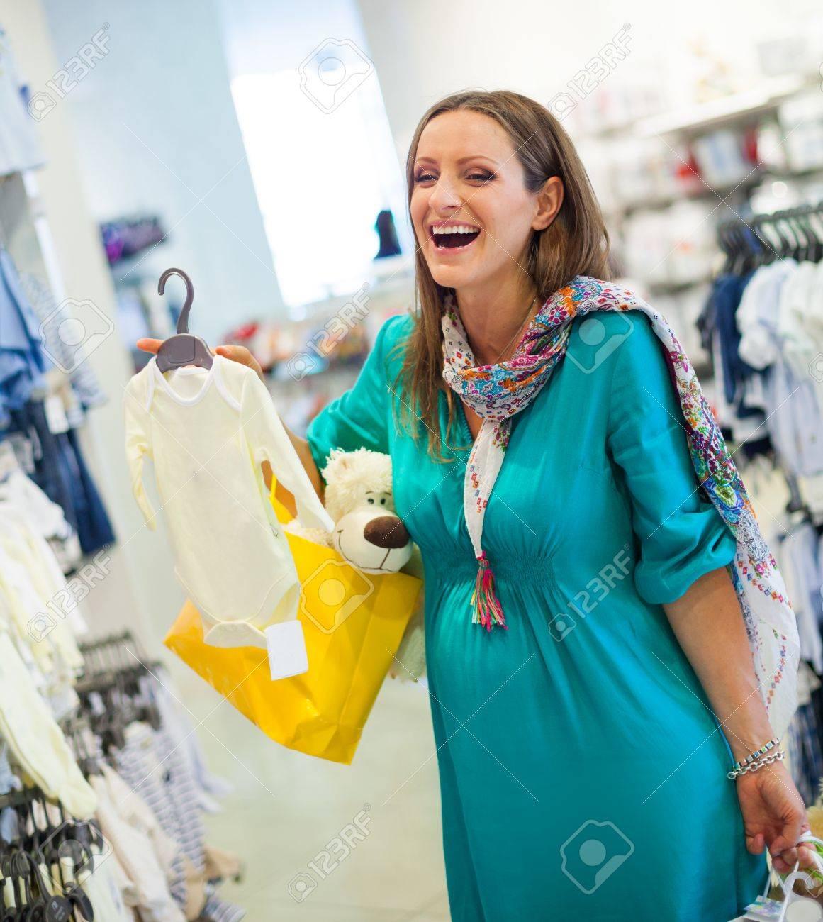 Young pregnant woman at clothes shop