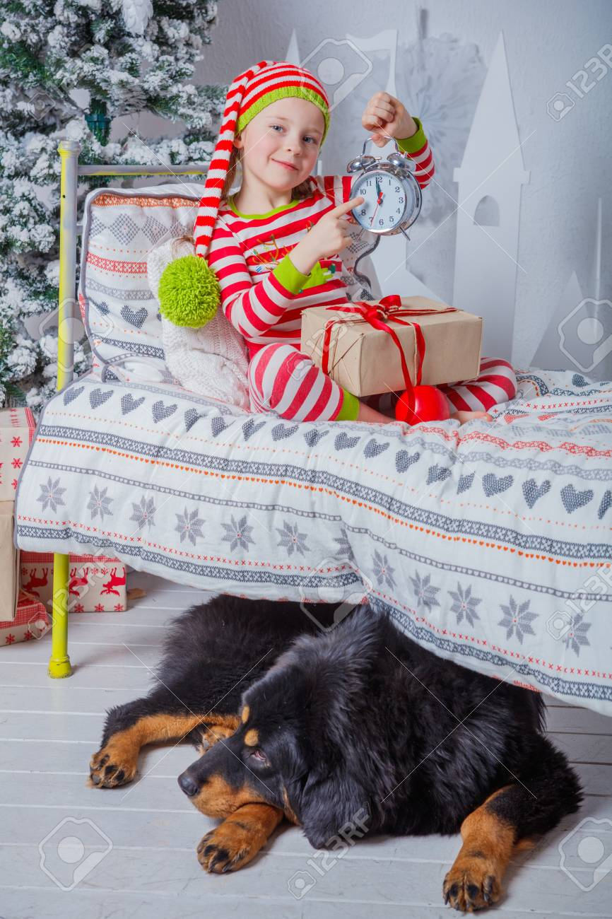 0567ba6af55388 Happy cute little girl dressed in striped pajamas sitting in decorated New  Year room at home