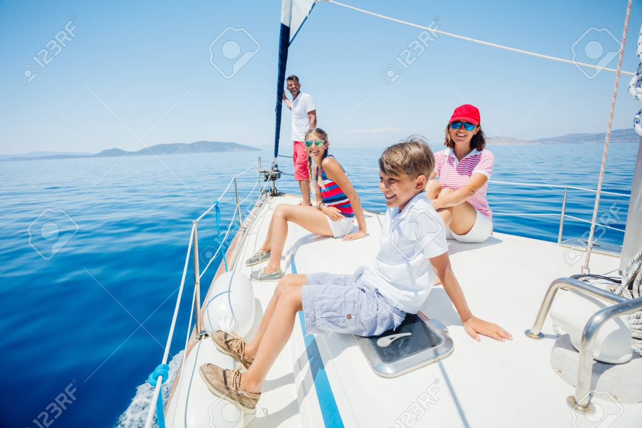 Boy with his sister and mother on board of sailing yacht on summer cruise. - 123377474