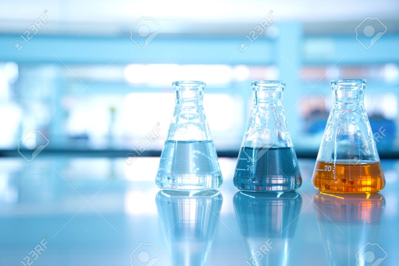 three flask of water black orange solution in science laboratory background - 72999168