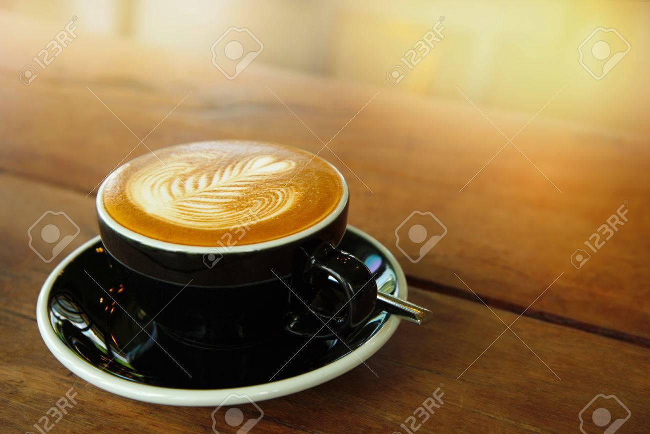 Tazza di caffè nero caldo bere sul tavolo in legno bar con sfondo