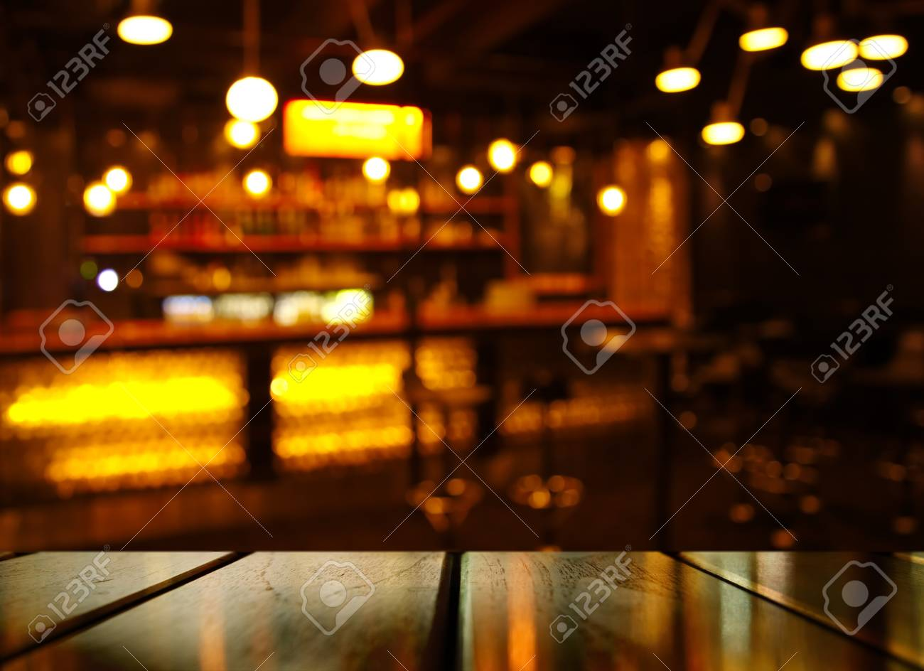 top of wood table with light reflection with yellow abstract blur bar or club in the dark night background - 86514187