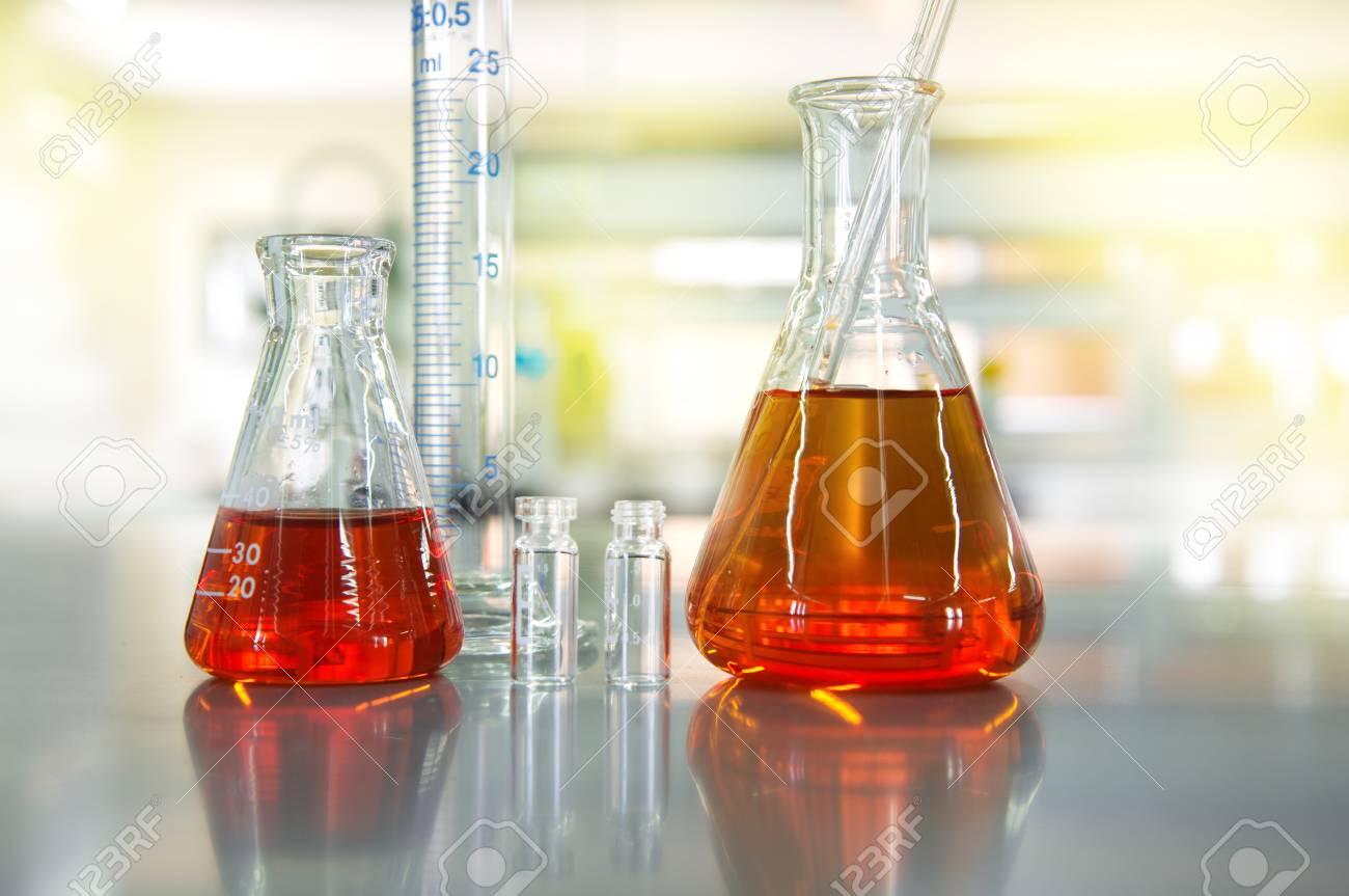 orange solution in flask cylinder vial in chemical science laboratory background - 88330450