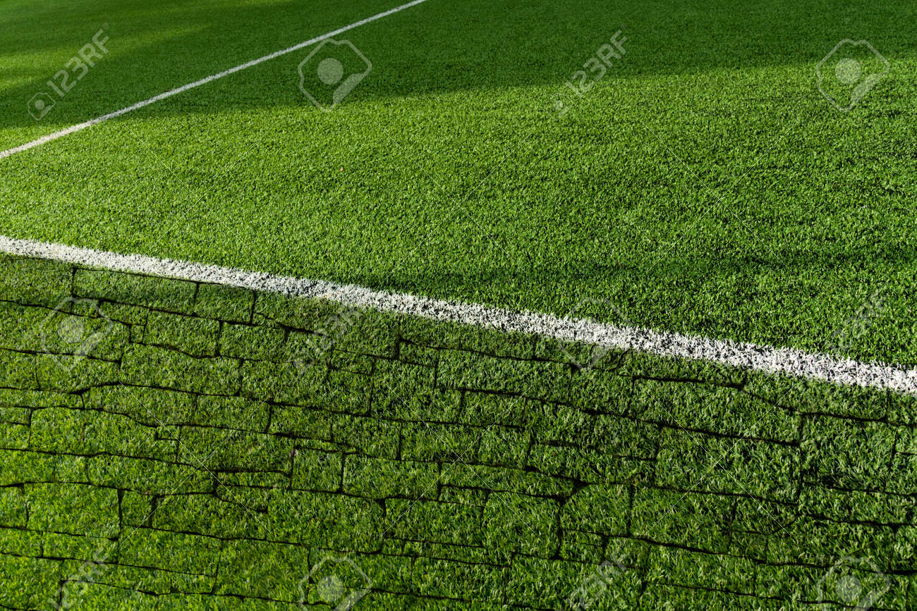 green artificial grass football or soccer field with white line and brick wall texture with sunlight background - 173812532