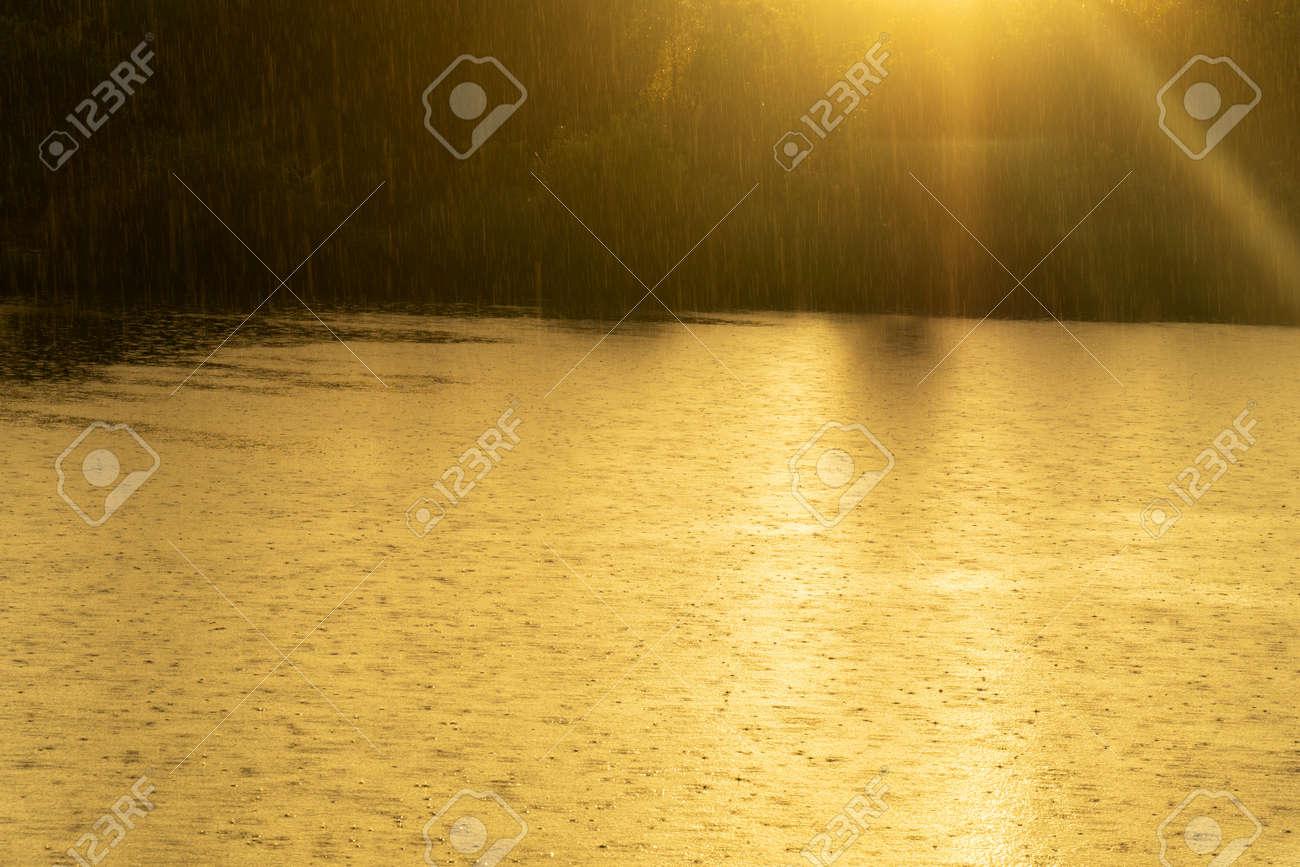 raining into the lake with orange sunlight nature landscape background - 173776298