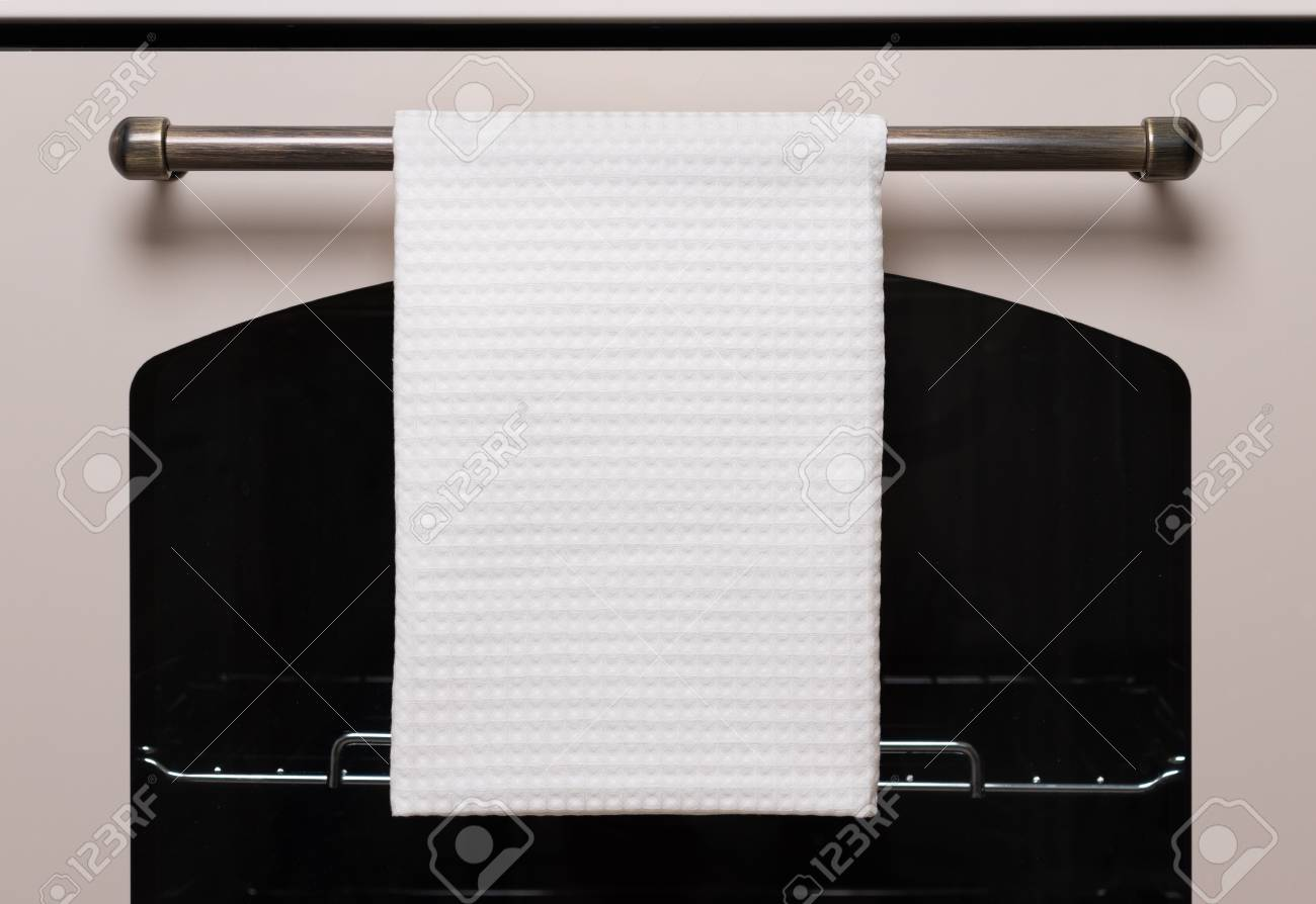 White kitchen towel hangs on the oven handle, product mockup