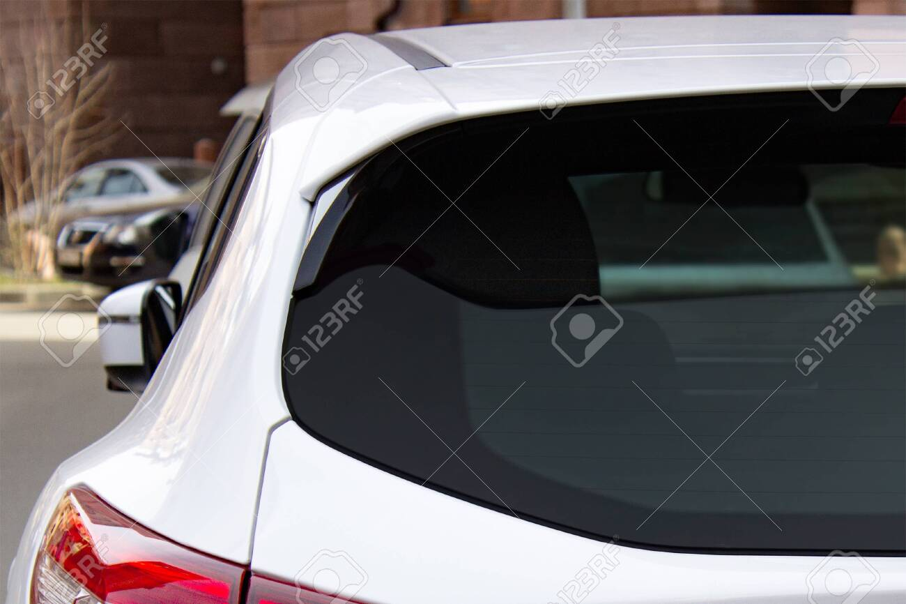 Back window of a white car parked on the street, rear view. Mock-up for sticker or decals - 144144351