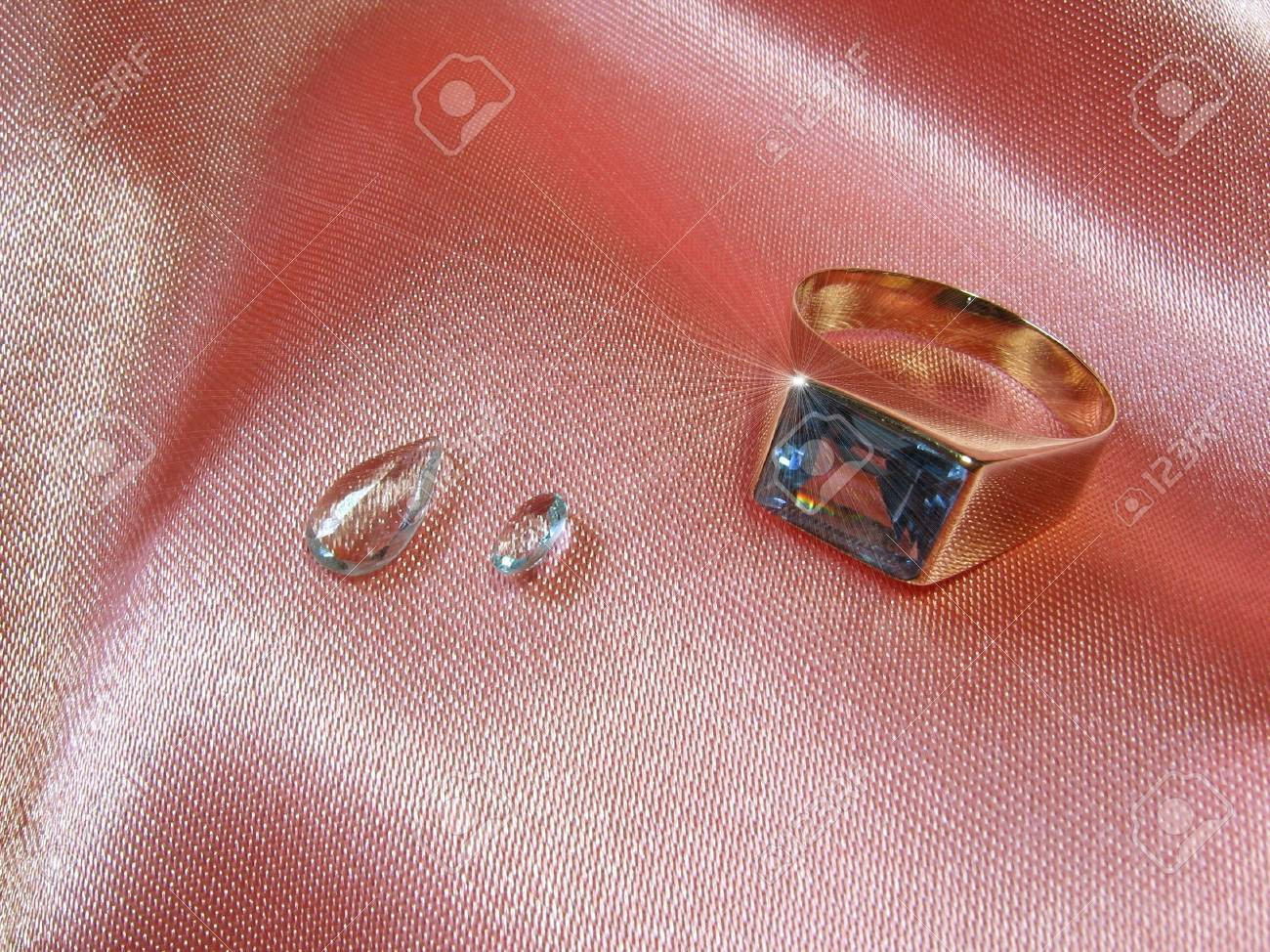 An Aquamarine Gold Ring With Two Gems On Pink Satin. The Sparkle ...