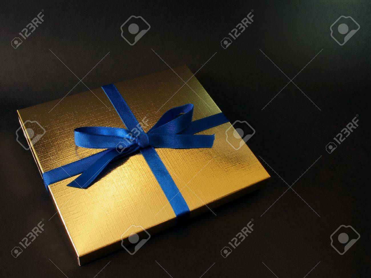 Close up view of a gold gift box with blue bow on black background, with copy space and exquisite lighting Stock Photo - 622785