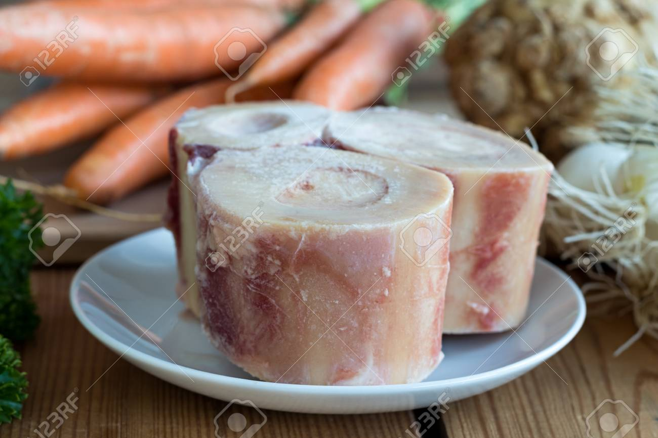 Ingredients for making a beef bone broth - marrow bones, carrots, onions, celery root - 81813148