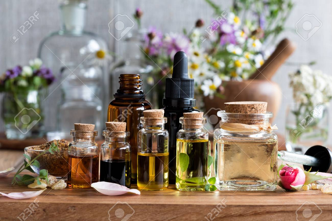 Selection of essential oils, with herbs and flowers in the background - 82809057