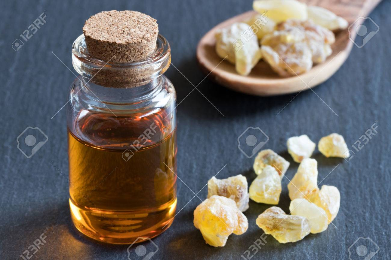 A bottle of frankincense essential oil with frankincense crystals in the background - 82871432