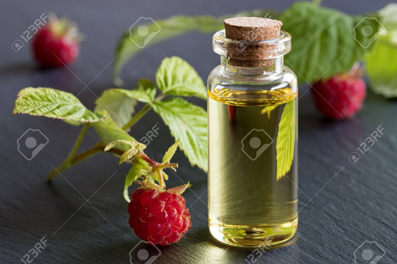 A bottle of raspberry seed oil with raspberries on a dark background - 83090459