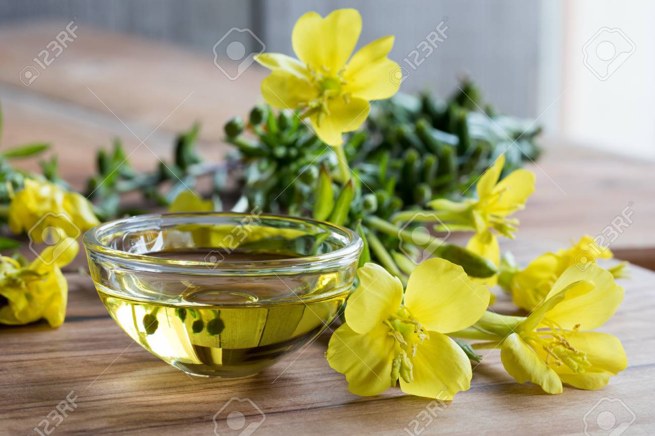 Evening primrose oil in a glass bowl, with fresh evening primrose flowers in the background - 87635230