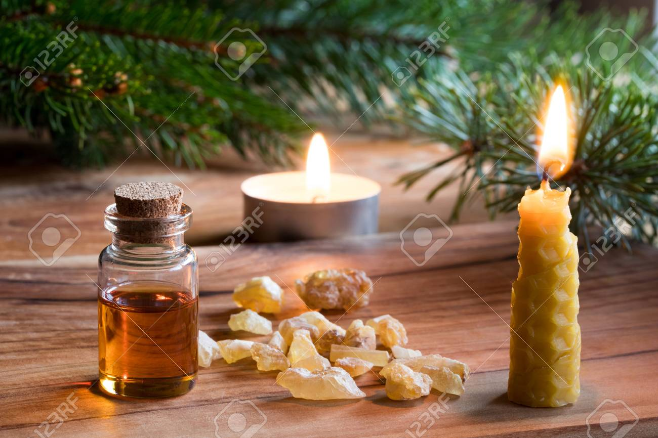 A bottle of frankincense essential oil with frankincense resin crystals, a candle made from beeswax, and spruce and pine branches in the background. Christmas styled. - 90076931