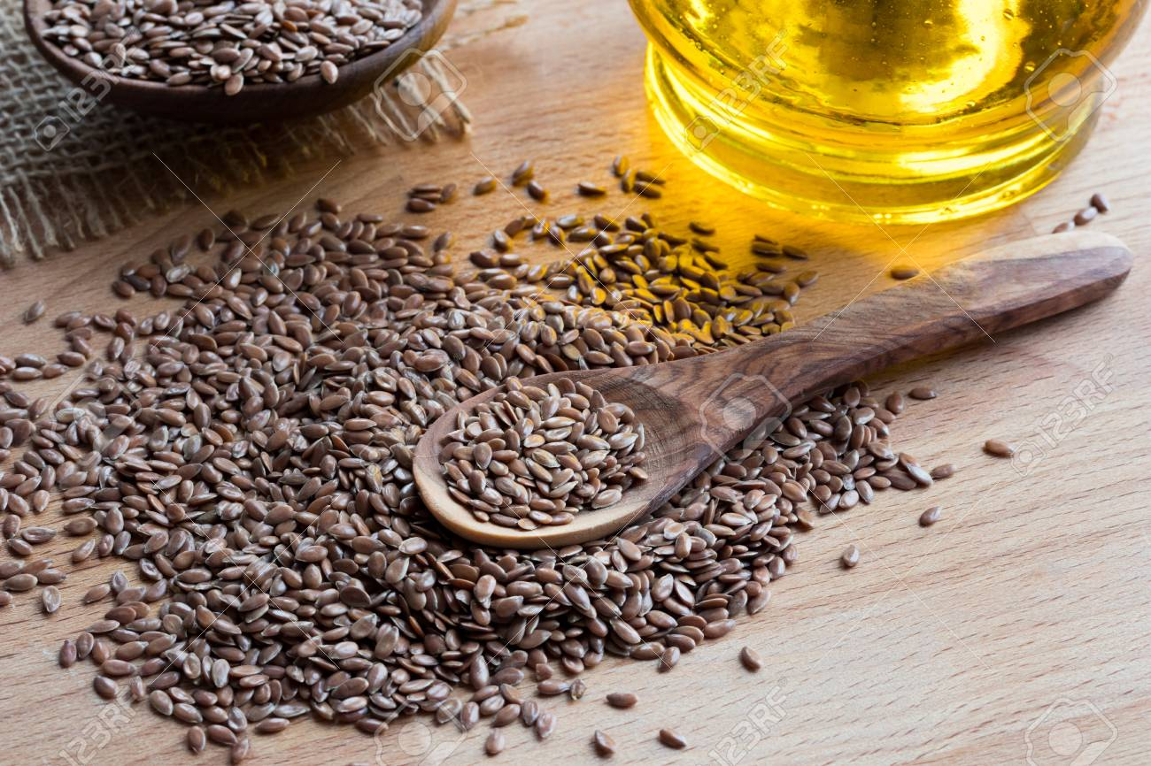 Flaxseed On A Wooden Spoon With Flaxseed Oil In The Background