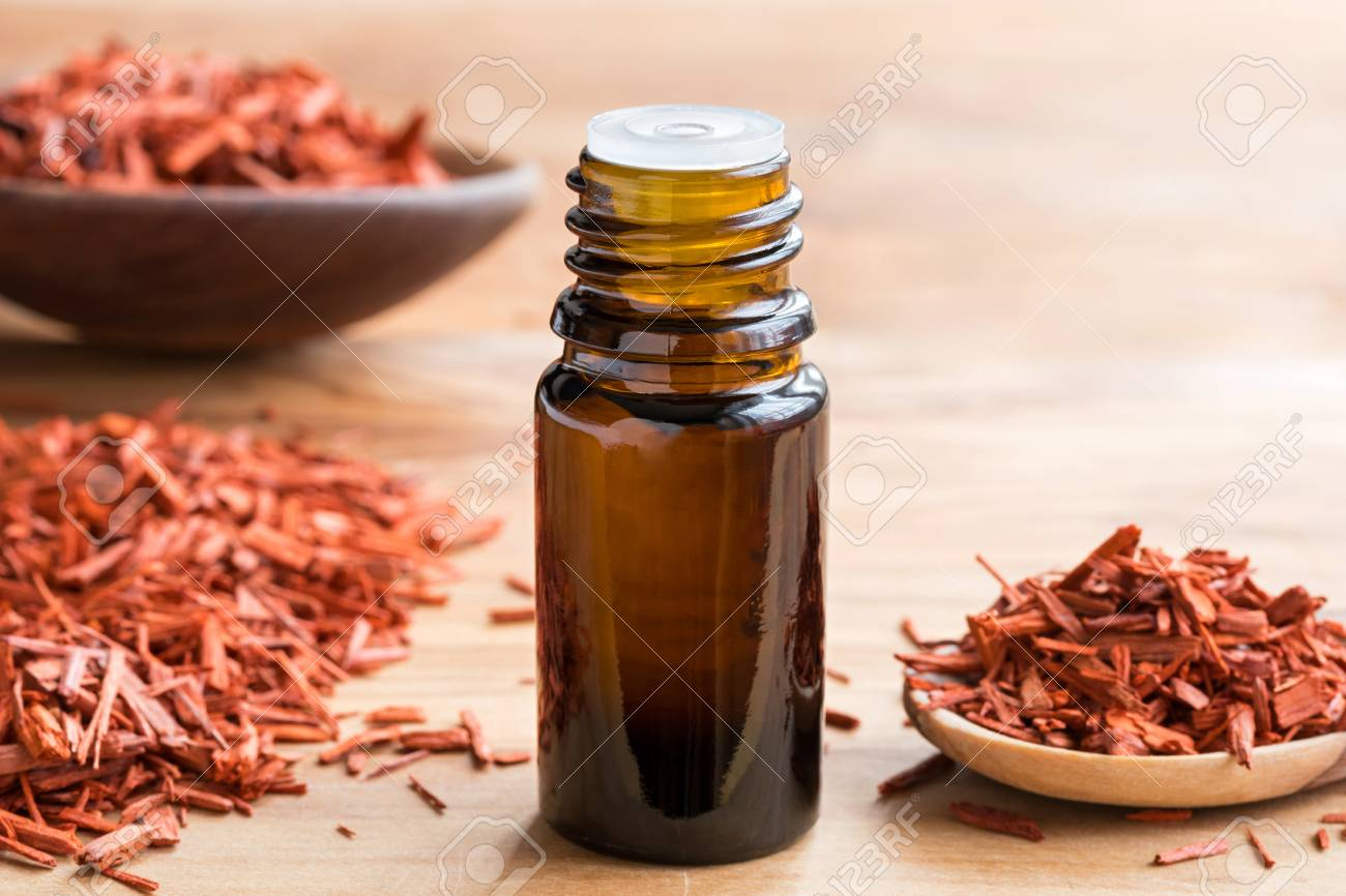 A bottle of sandalwood essential oil on a wooden table, with sandalwood in the background - 93413307