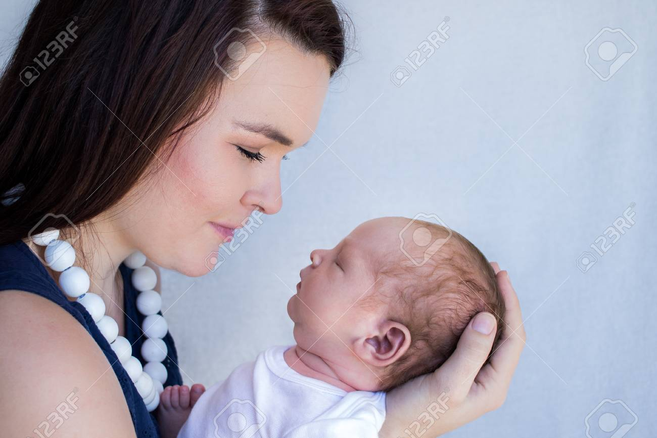 Mother holding newborn baby closeup of faces side profile stock photo 113477084