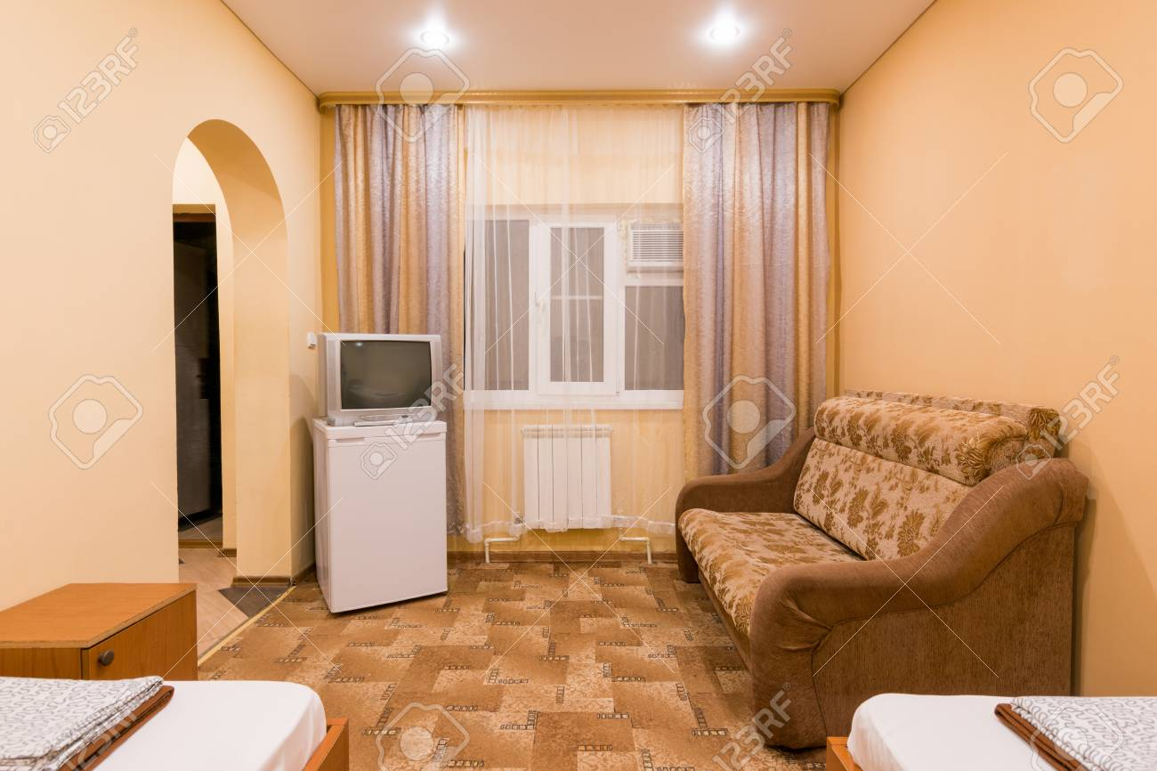 The interior of a small room with sofa bed and two single beds, window, TV and fridge - 71934637