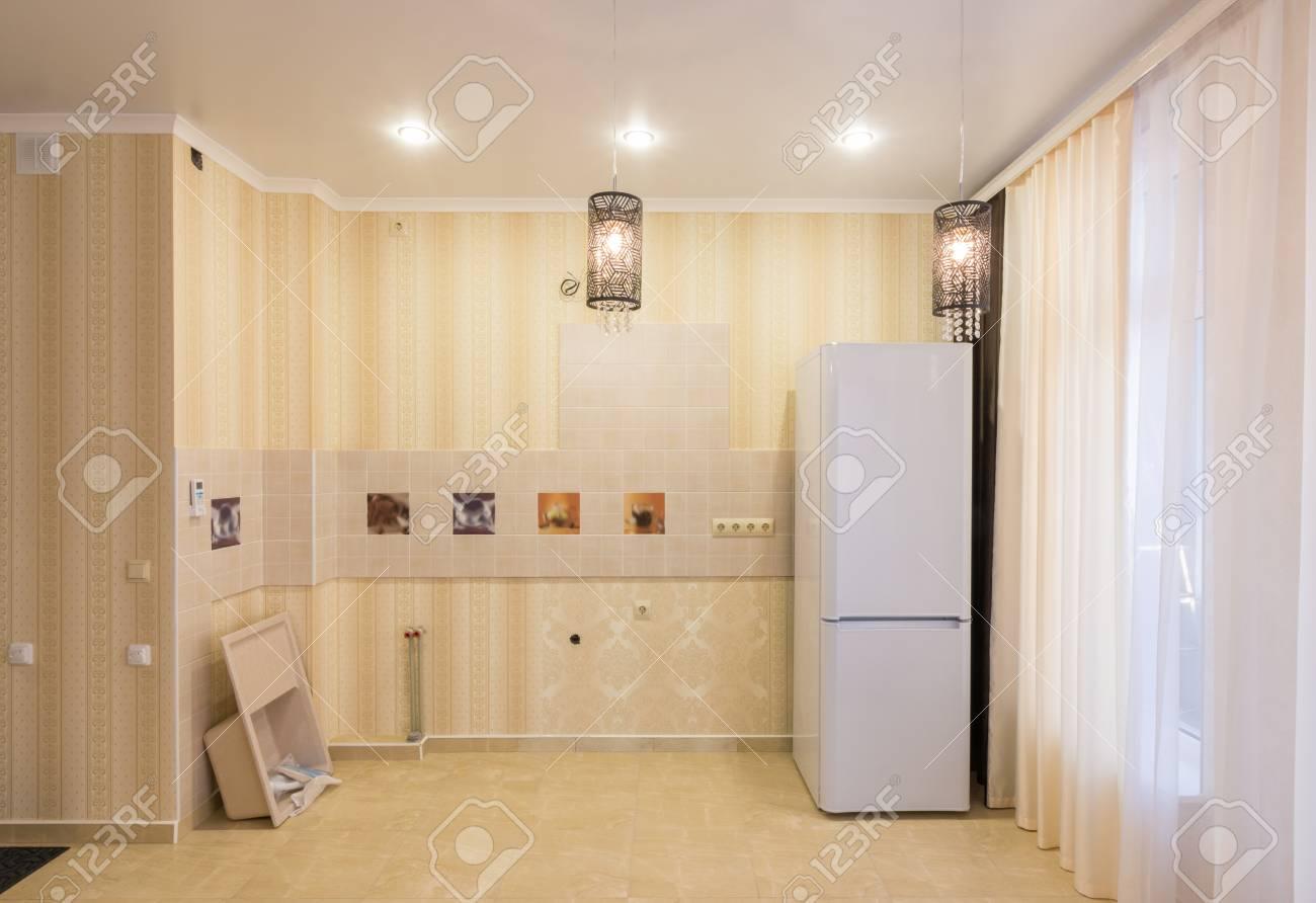 Interior de una cocina vacía sin muebles, hay un fregadero y un refrigerador