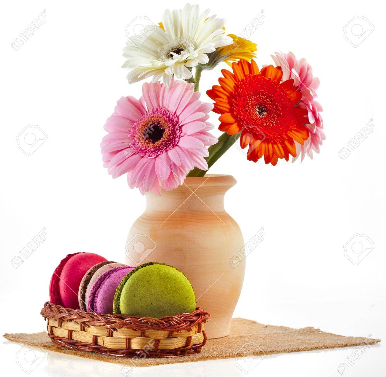 Colorful macaroons and bouquet gerber in vase isolation on a white background Stock Photo - 18932106