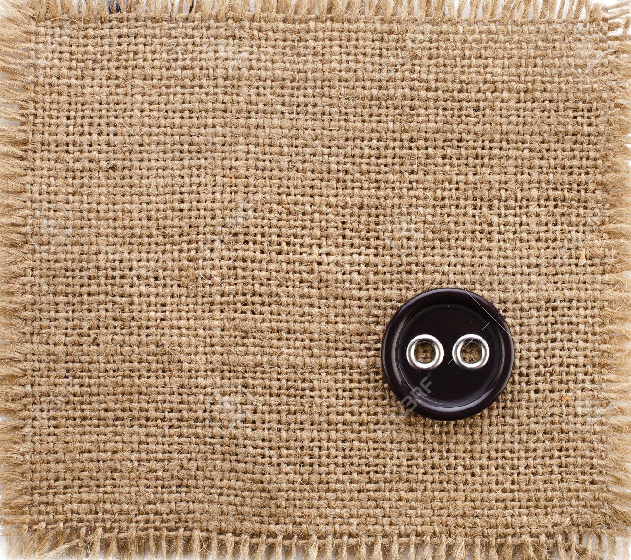85b8fc795 Foto de archivo - Viejo botón negro sobre tela arpillera textura de fondo