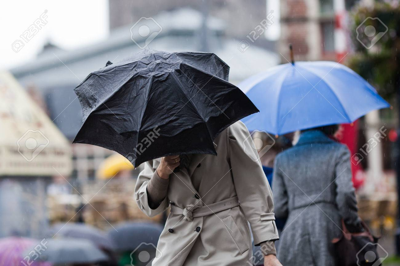 people walking with umbrellas in the rainy city - 53689899