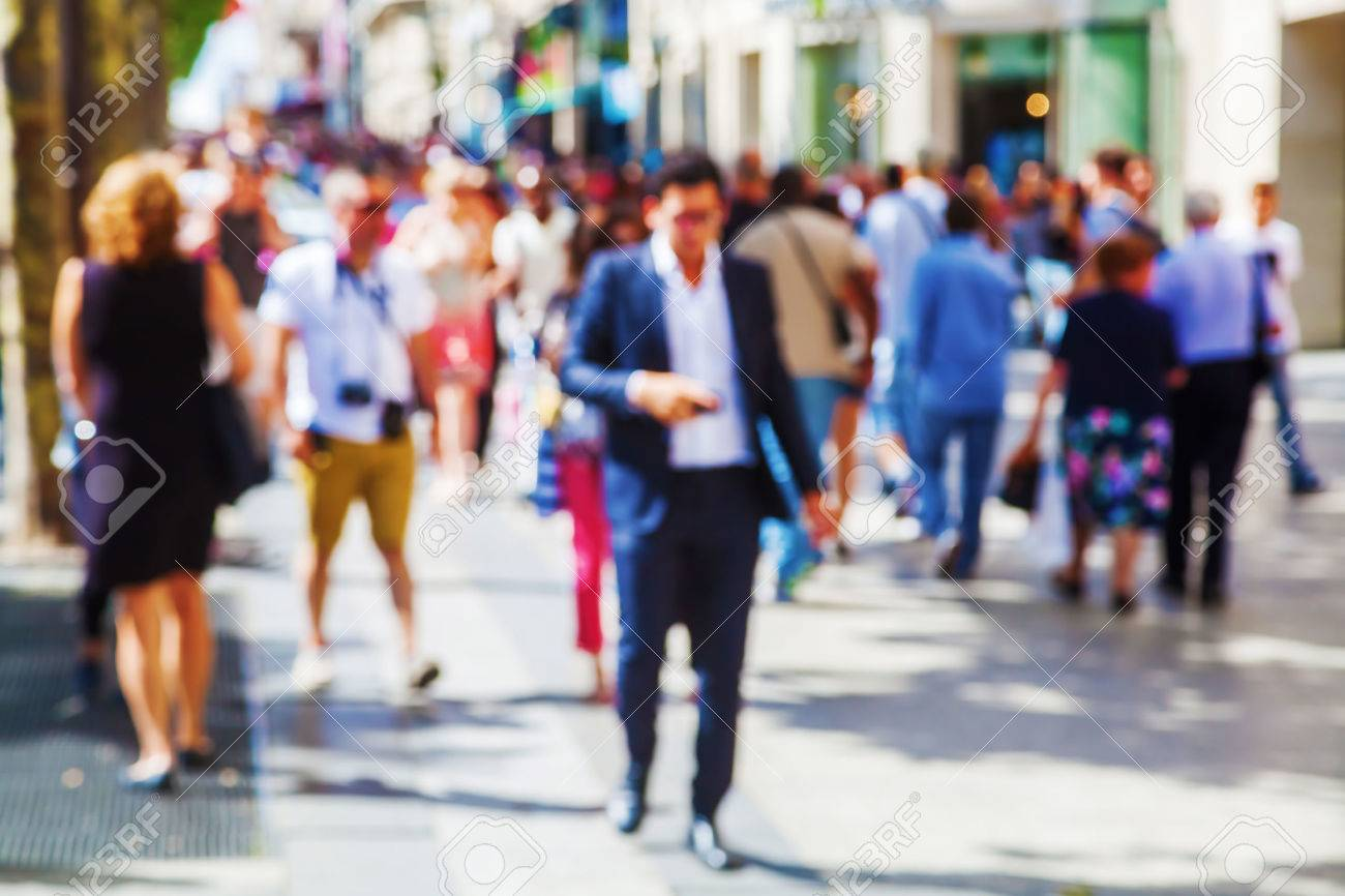 out of focus picture of a crowd of people walking in the city - 54581710